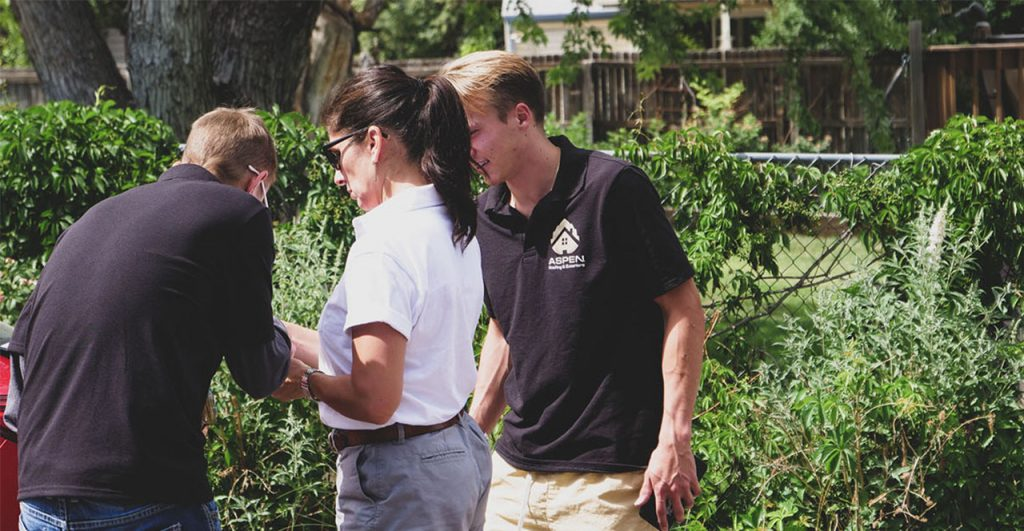 Two Aspen Roofing employees smile as they meet with an adjuster near a vine covered fence.