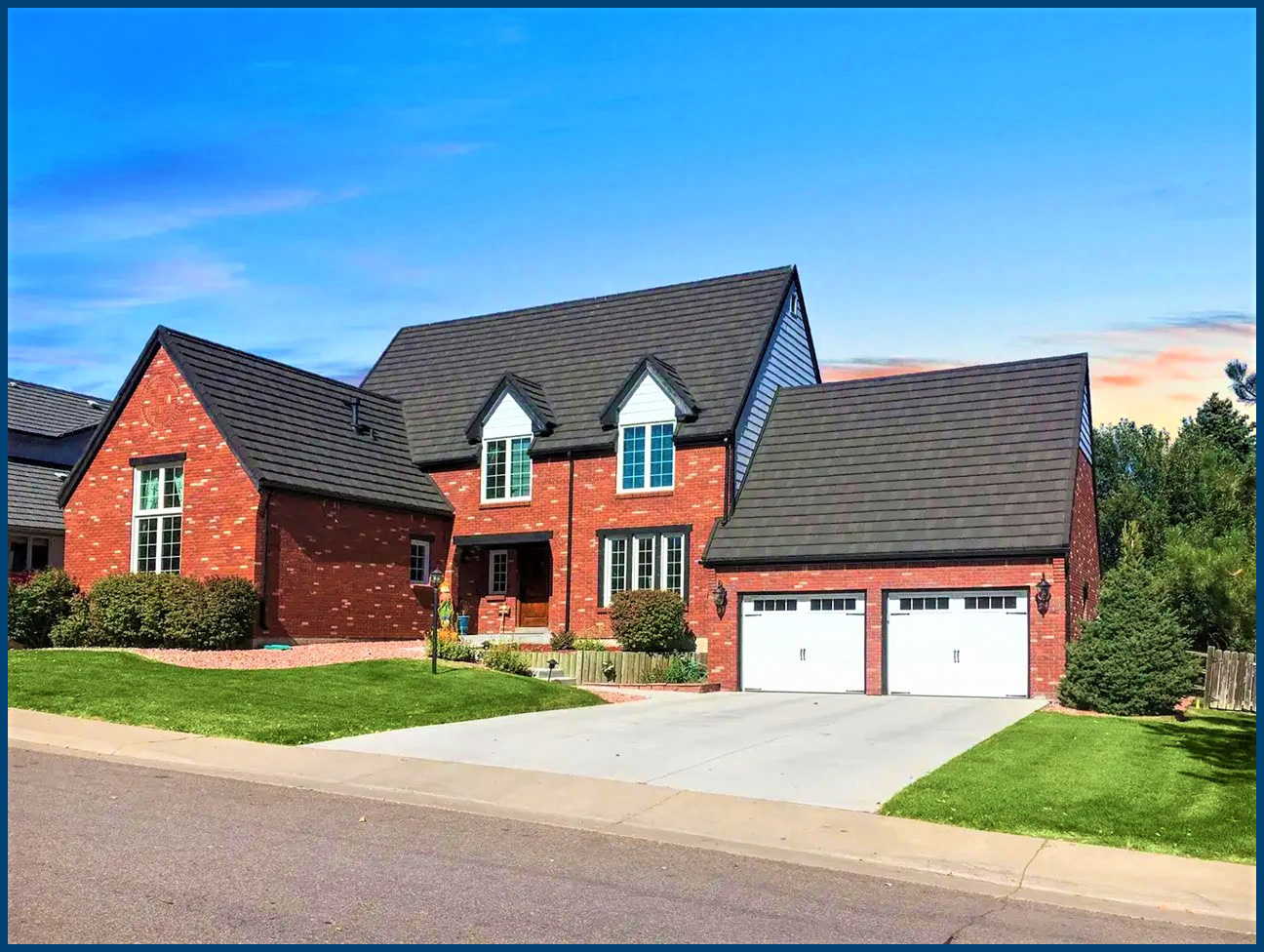a red brick home sits in a small plot of land with dark, charcoal colored roofing shingles.