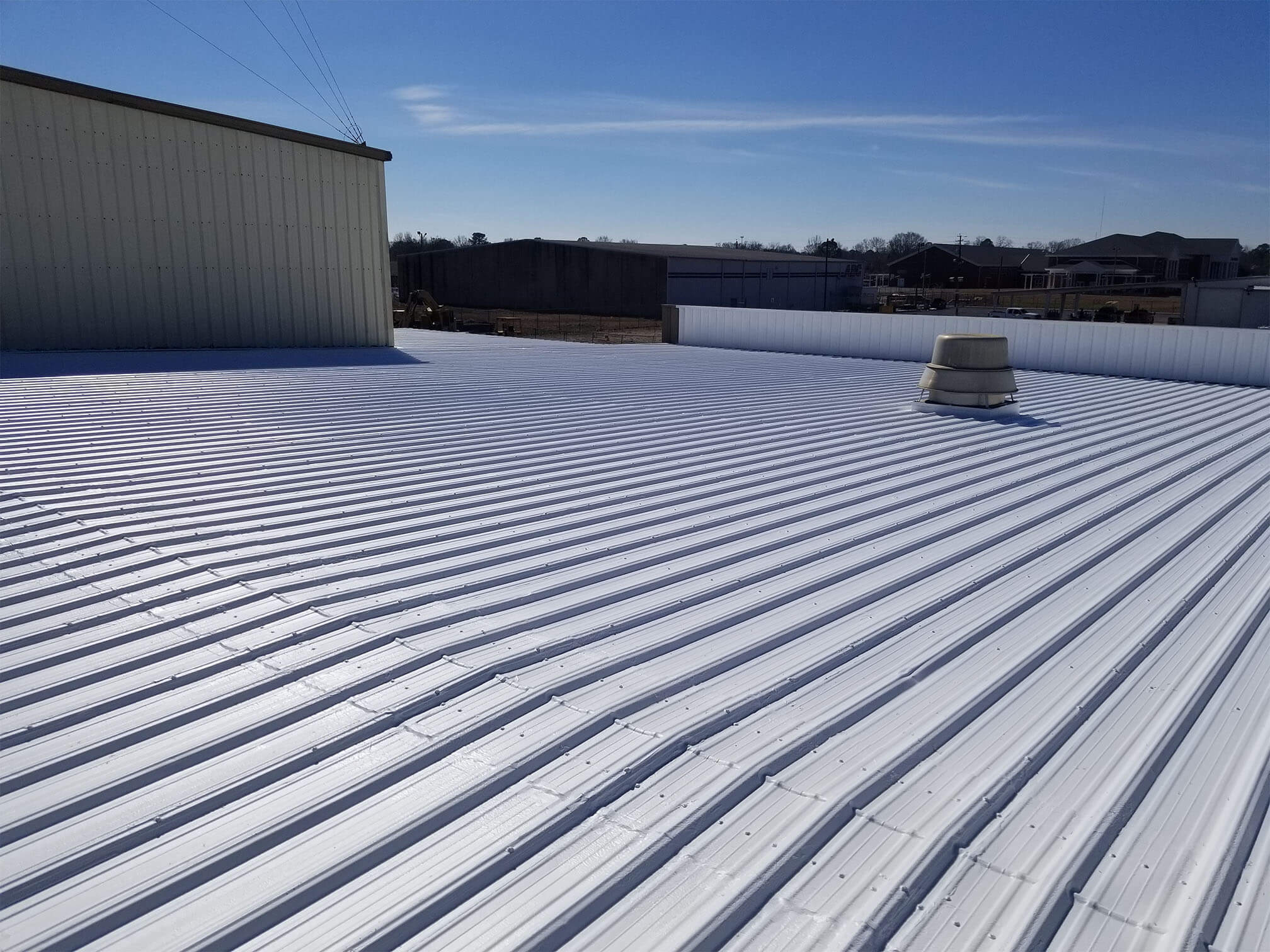 A ridged, metal roof has a white coating on it, reflecting the sun.