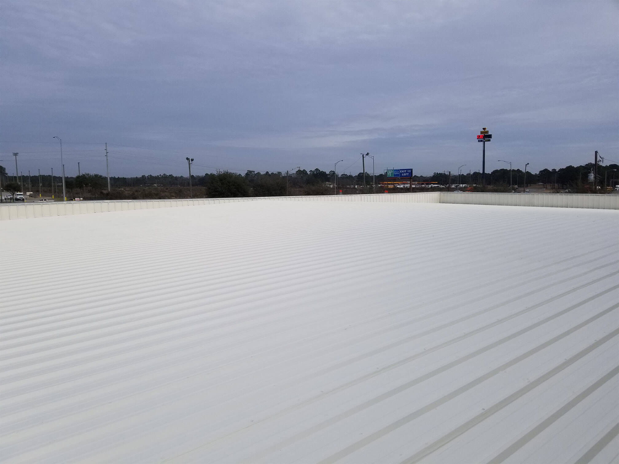 a riveted flat metal roof is base coated with an ivory fluid to prepare it for it's final coat