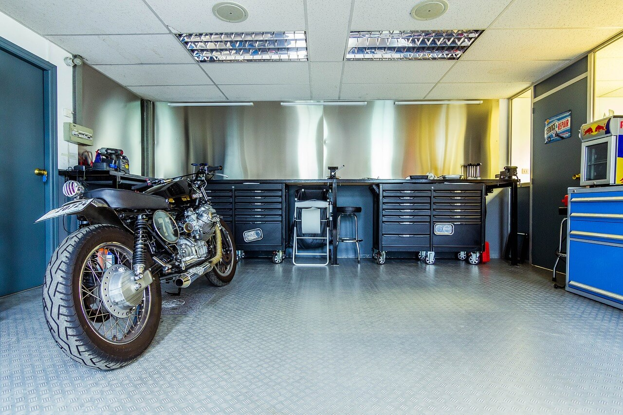 A black motorcycle sits comfortably inside of a dry garage