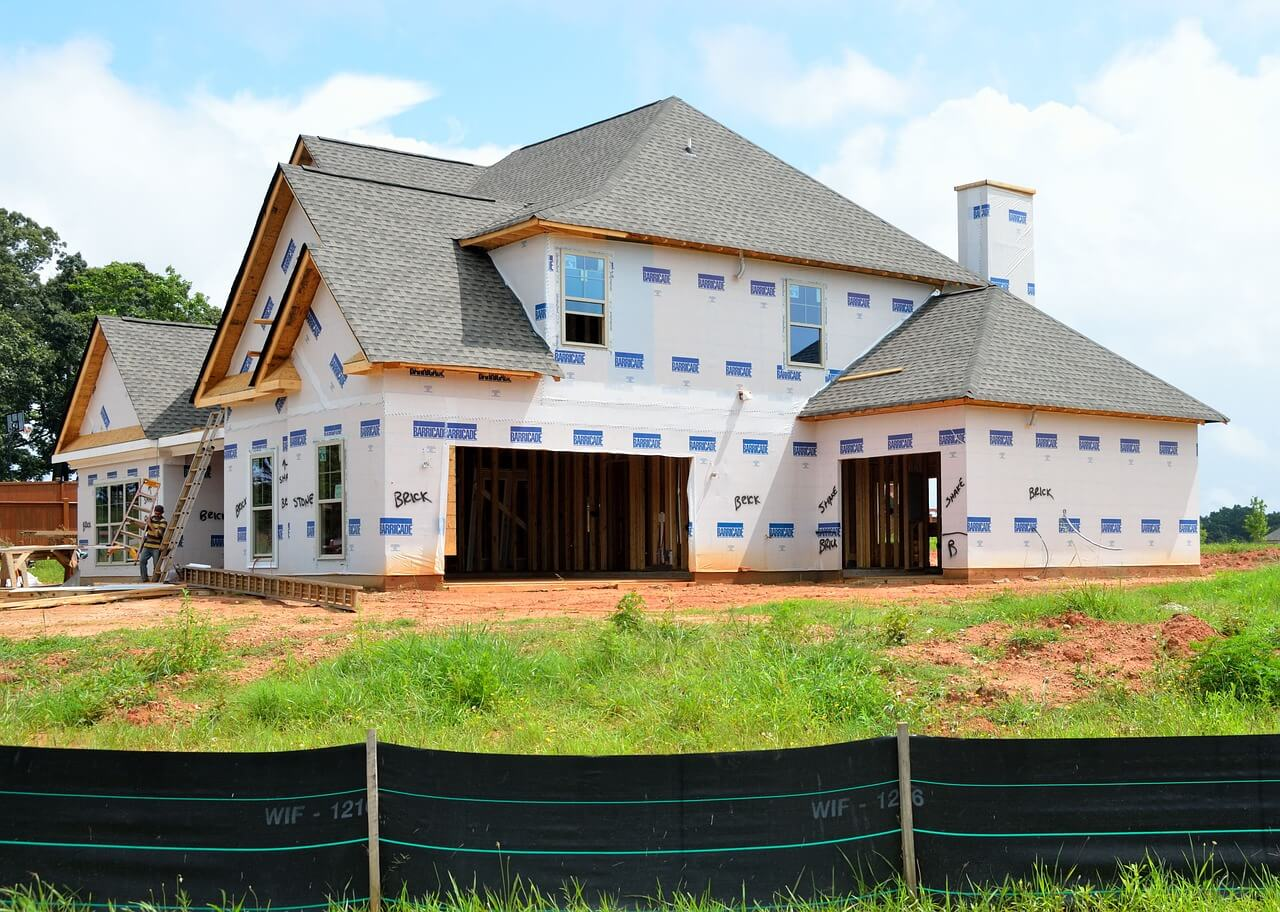 A home under construction with framing an plywood complete. The roof has been fully installed while the rest of the home awaits completion.