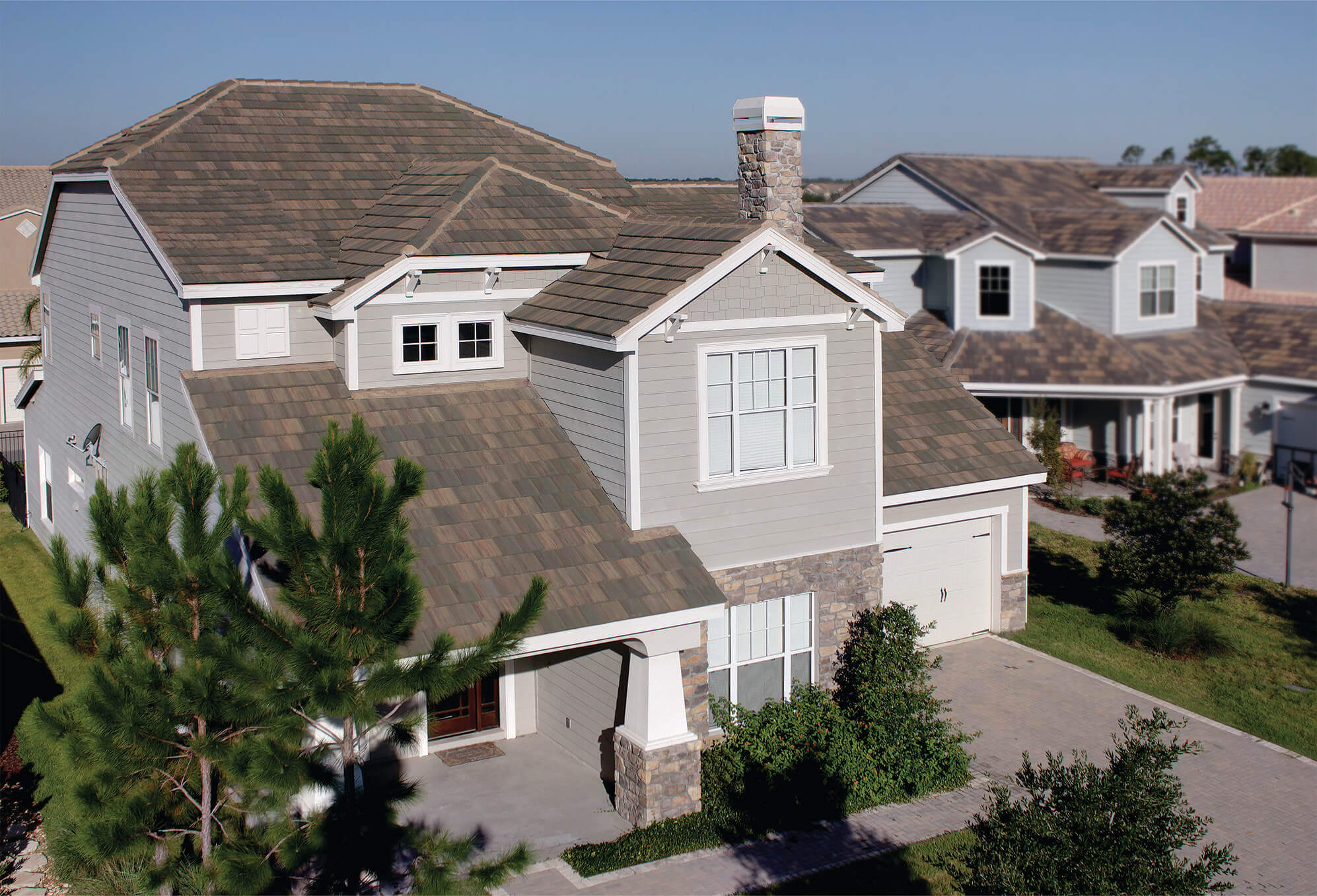 Grey two story home with white trim rests in a suburban neighborhood, protected by dark grey and brown concrete shingles.
