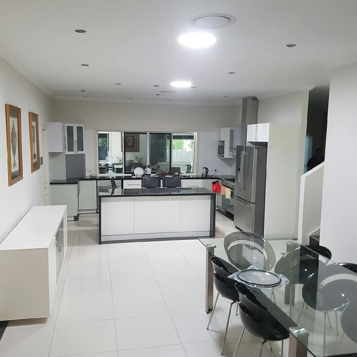 Tube shaped skylights allow brilliant light into a white kitchen with a glass table.