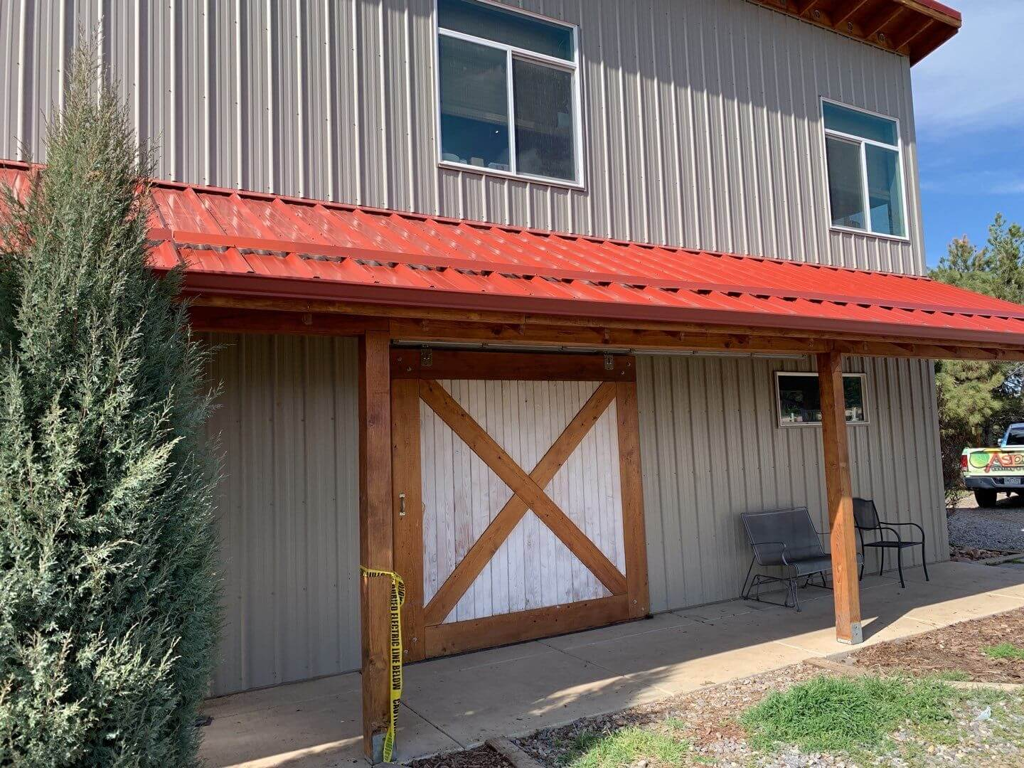 Red metal standing seam roof protects a barn style home from the elements.