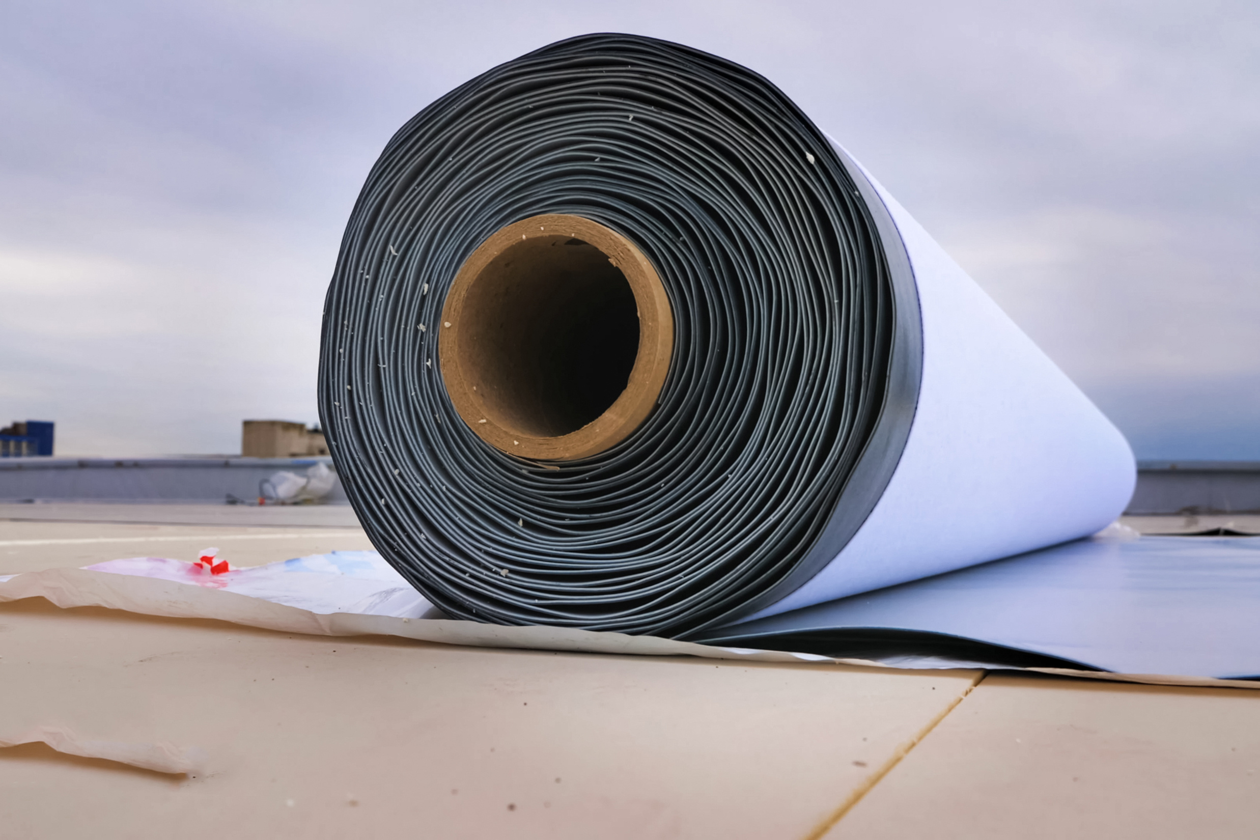 White, rubberized material is rolled up and resting on a flat roof ready to be installed.